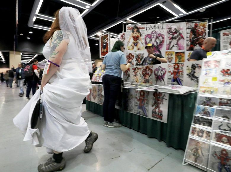 Conventiongoers at last year's Emerald City Comic Con browse the booth of artist Jamie Tyndall. Tyndall will be at this year's ECCC. Some creators and exhibitors are wrestling with whether to attend ECCC this year, given coronavirus concerns. (Alan Berner / The Seattle Times, file)