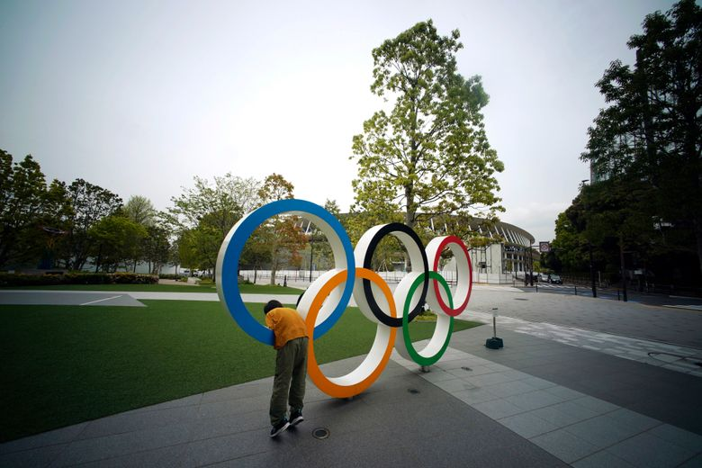 FILE – In this Tuesday, April 21, 2020, file photo, a child plays at the Olympic rings in front of the New National Stadium in Tokyo. A staff member of the Tokyo Olympic organizing committee has tested positive for COVID-19, according to Tokyo organizers in a statement released on Wednesday.  (AP Photo/Eugene Hoshiko, File)