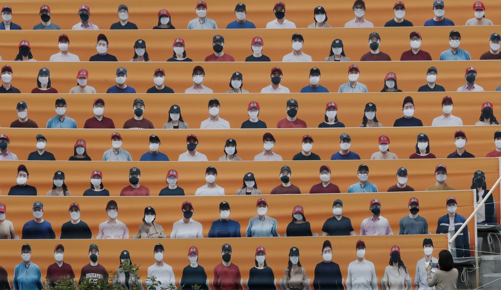 A woman holds her smartphone in front of the spectators' seats which are covered with pictures of fans, before the start of a baseball game between Hanwha Eagles and SK Wyverns in Incheon, South Korea, May 5. (Lee Jin-man / The Associated Press)