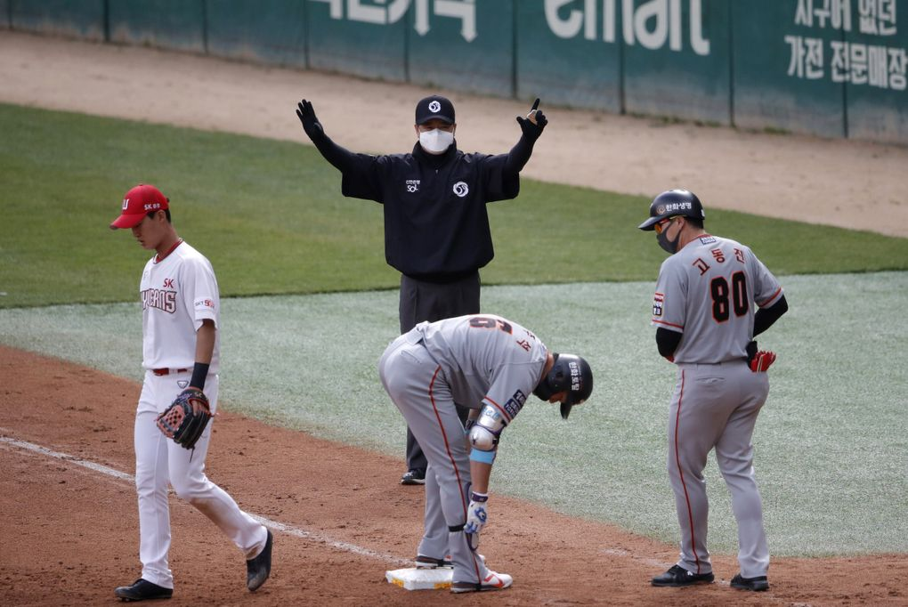 First base umpire Lee Ki-joong, wearing a mask and gloves as a precaution against the new coronavirus, makes a call during a game between the Hanwha Eagles and SK Wyverns in Incheon, South Korea, on Tuesday. (Lee Jin-man / The Associated Press)