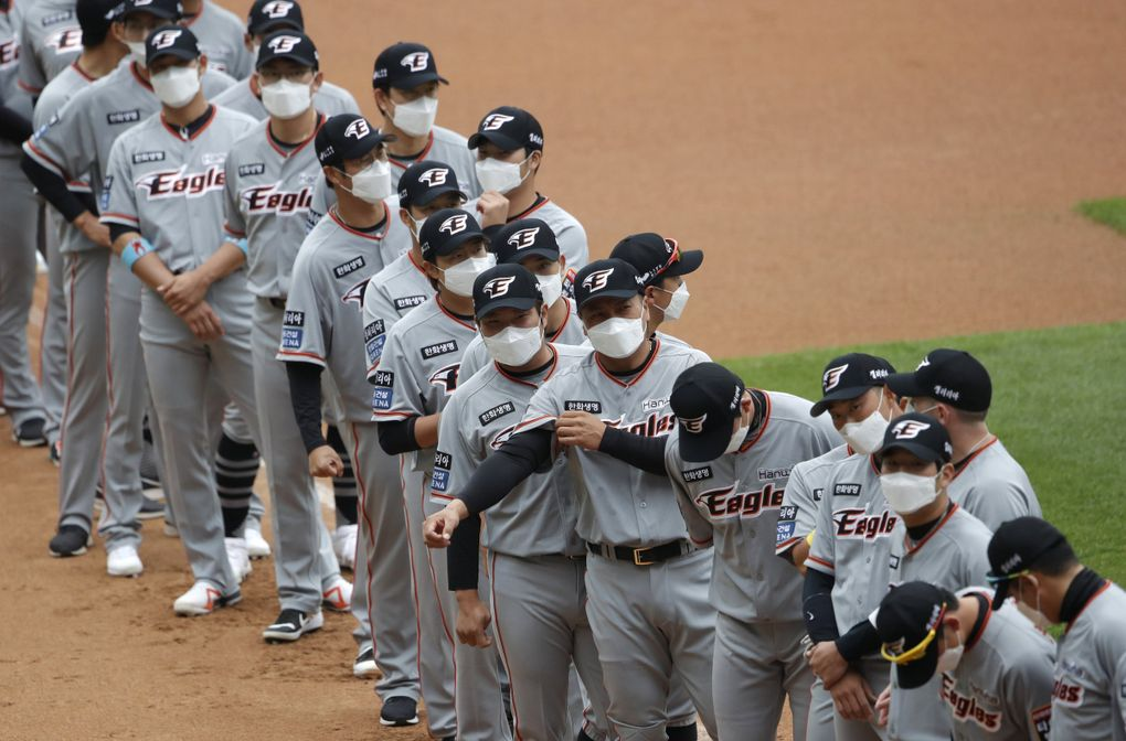 Hanwha Eagles players wearing face masks line up during the start of their regular season game against SK Wyverns in Incheon, South Korea, May 5. (Lee Jin-man / The Associated Press)