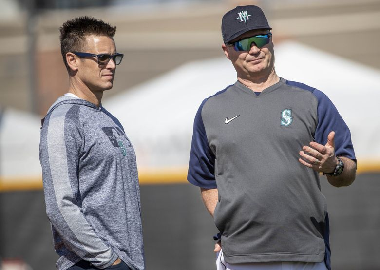 Jerry Dipoto, left, talks with manager Scott Servais during spring training on Feb. 17, 2020. (Dean Rutz / The Seattle Times)