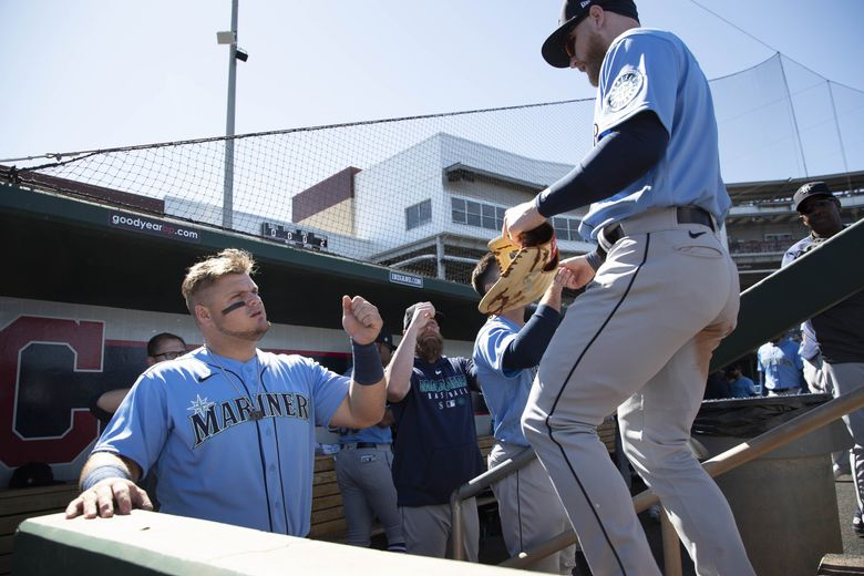 Daniel Vogelbach welcomes centerfielder Jake Fraley back into the Mariner dugout between innings Wednesday.  The Seattle Mariners played the Cincinnati Reds in spring training baseball Wednesday, February 26, 2020 in Goodyear, Arizona. (Dean Rutz / The Seattle Times)