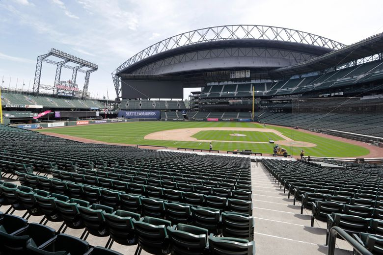 In an otherwise empty ballpark, grounds crew members continue to keep the Seattle Mariners' field in playing shape as the ballpark goes into its seventh week without baseball played because of the coronavirus outbreak Monday, May 11, 2020, in Seattle. A person familiar with the decision tells The Associated Press that Major League Baseball owners have given the go-ahead to making a proposal to the players' union that could lead to the coronavirus-delayed season starting around the Fourth of July weekend in ballparks without fans. (AP Photo/Elaine Thompson)