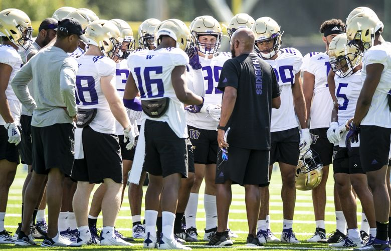 Jimmy Lake, now head coach of the Huskies, talks with the UW defense during football training camp last year. Numerous reports today suggest that college football may be canceled for the fall. (Bettina Hansen / The Seattle Times, 2019)