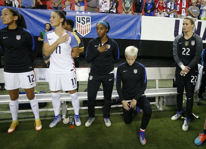 USA's Megan Rapinoe, right, kneels next to teammates Christen Press (12), Ali Krieger (11), Crystal Dunn (16) and Ashlyn Harris (22) as the US national anthem is played before an exhibition soccer match against Netherlands Sunday, Sept. 18, 2016, in Atlanta. (John Bazemore / AP)