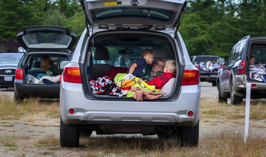 """Logan Miller, 6, whispers something to his mom, Cassie, as brother Easton, 9, sits at right in the family car as they settle in before """"The Goonies"""" starts at the Skyline Drive-In in Shelton. (Ellen M. Banner / The Seattle Times)"""
