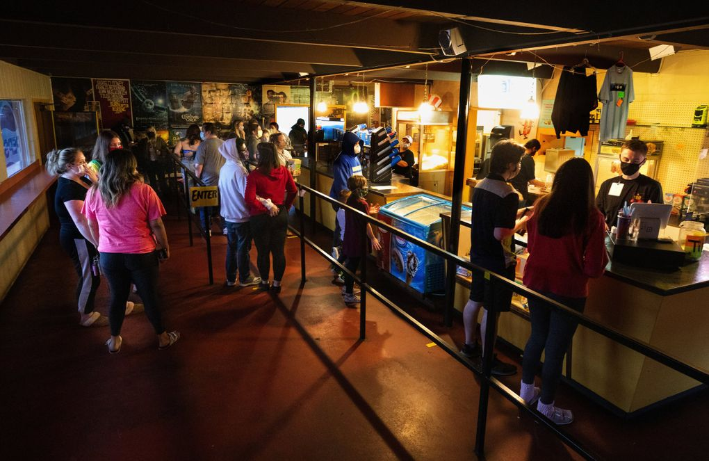 Cashier Chase Rollins, right, waits on customers in the snack bar at the Skyline Drive-In in Shelton. Customers are only allowed to enter the snack bar through one door, must practice social distancing while in line, wear masks and exit through another door. (Ellen M. Banner / The Seattle Times)