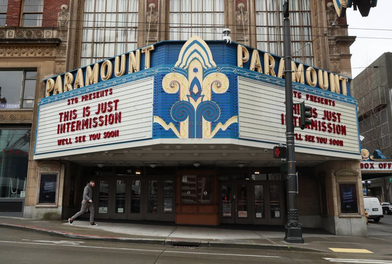 A pedestrian walks past a closed Paramount Theatre in Seattle. Seattle Theatre Group's theaters — the Paramount, Moore and Neptune — have been shuttered since March due to the coronavirus pandemic. (Erika Schultz / The Seattle Times, March 26)