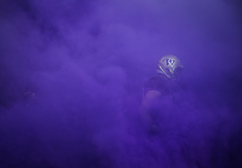 A Washington player emerges from the tunnel, surrounded by purple smoke, as the team streams onto the field at Husky Stadium on Saturday, Oct. 22, 2016. Washington beat Oregon State 41-17 to remain unbeaten.   (Lindsey Wasson / The Seattle Times)