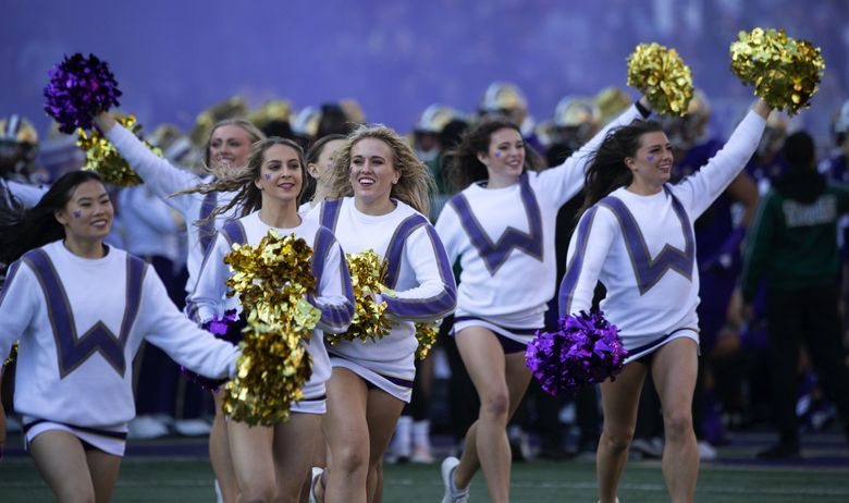 Washington Huskies cheerleaders lead the team onto the field as the University of Utah  plays the University of Washington Huskies at Husky Stadium in Seattle on November 2, 2019.  (Mike Siegel / The Seattle Times)