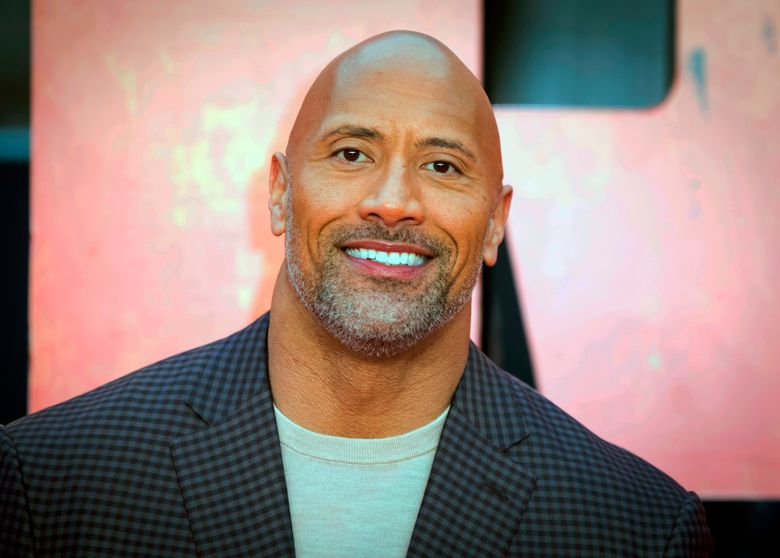 """In this April 11, 2018, file photo, actor Dwayne Johnson poses for photographers at the premiere of the """"Rampage,"""" in London. (Photo by Vianney Le Caer/Invision/AP, File)"""