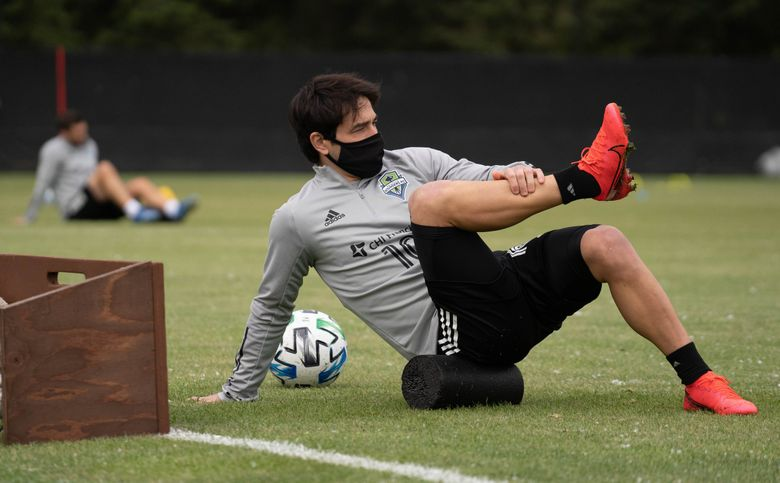 Sounders midfielder Nicolás Lodeiro and his teammates practice social distancing as they stretch at practice May 18 at Starfire Sports in Tukwila.  (Paul-Michael Ochoa / Sounders FC)