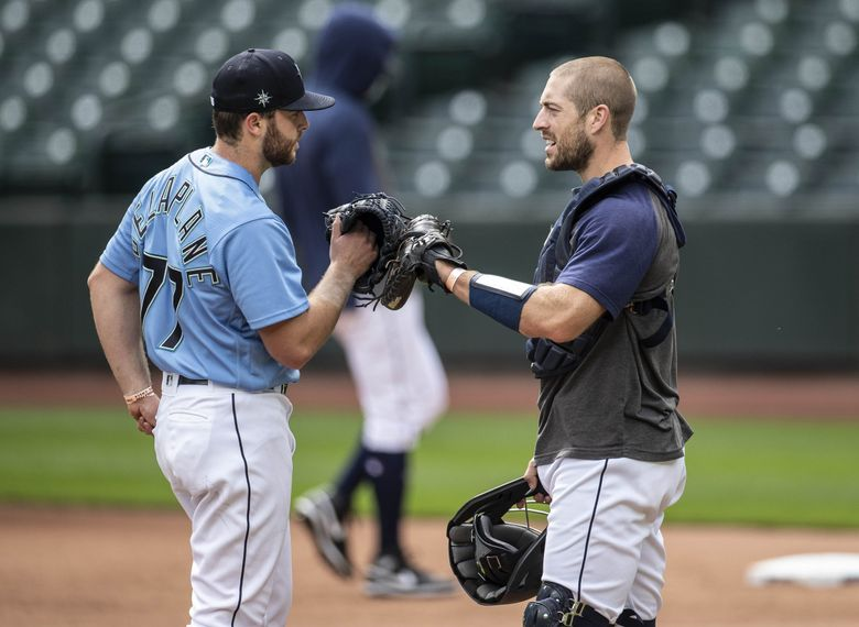 Sam Delaplane talks with catcher Tom Murphy before he is to throw to live hitters Tuesday. (Dean Rutz / The Seattle Times)