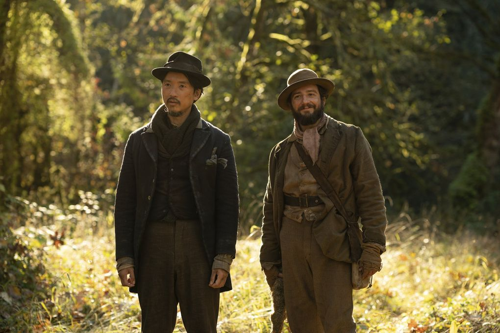 """""""First Cow,"""" starring Orion Lee (left) and John Magaro, follows the tale of an unlikely friendship in 1820s Oregon. (Allyson Riggs / A24 Films via AP)"""