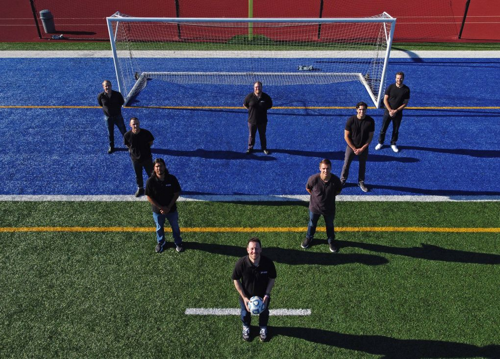 Teammates and friends of University of Washington soccer player Daniel Phelps, who died in his sleep of sudden cardiac arrest in 2015, stand on the Shoreline Stadium soccer field, Monday, July 13, 2020. Adam Lang, in front at the point; and Taylor Hoss, next row, left; helped organize, with a few of Phelps' teammates, an annual charity golf tournament – the DP Open – to honor their teammate and raise awareness for sudden cardiac arrest.  214471 (Ken Lambert / The Seattle Times)