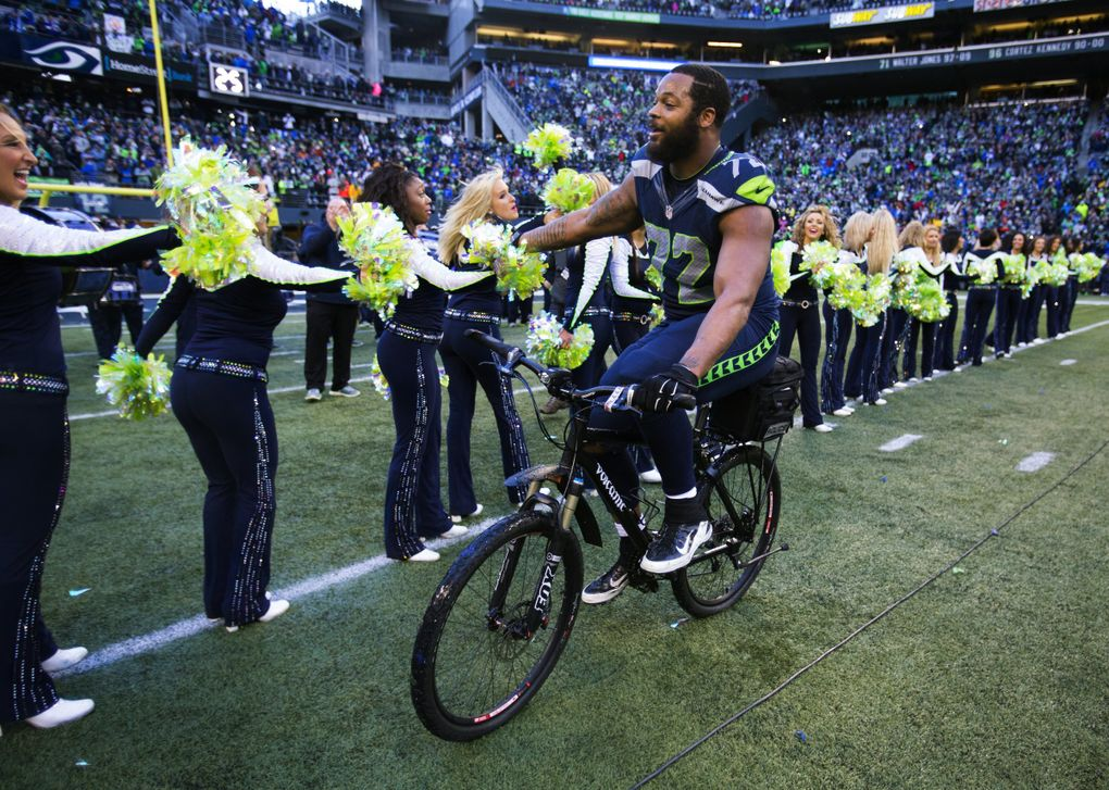 Seahawks defensive lineman Michael Bennett rides a police bike and offers high fives after Seattle defeated the Green Bay Packers in overtime to win the NFC championship at CenturyLink Field in 2015. (Dean Rutz / The Seattle Times)