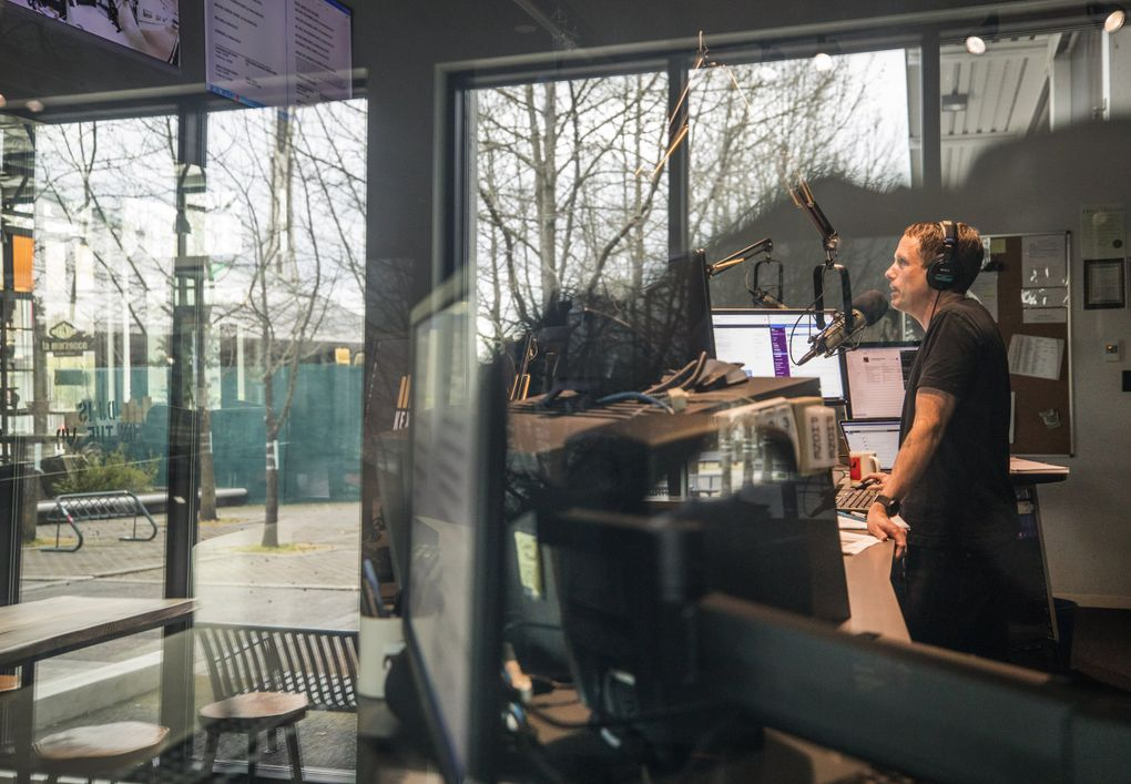 """John Richards, KEXP program director and host of """"The Morning Show,"""" in the main DJ booth during his show with a reflection of an empty Seattle Center Gathering Space Courtyard reflected in the window. (Steve Ringman / The Seattle Times)"""