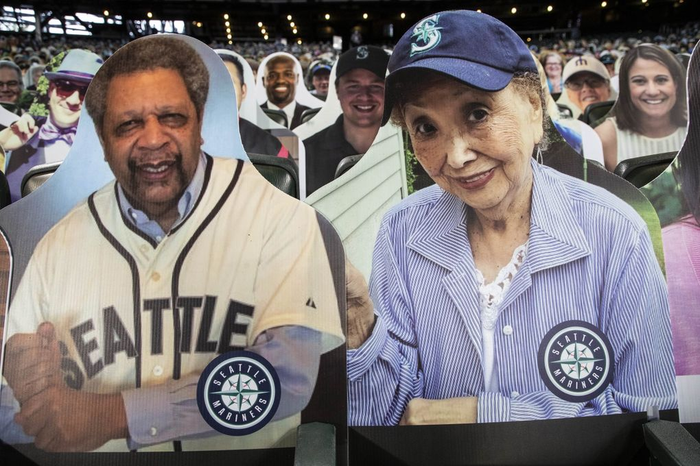 Atsuko Lile, aka Mama San, is an 87-year-old fan undergoing chemotherapy, and has a cutout next to Sonics legend Fred Brown. (Dean Rutz / The Seattle Times)