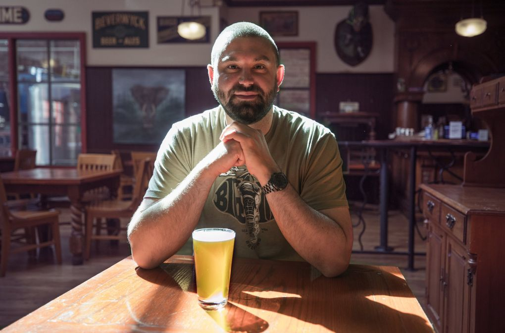Big Time Brewing owner Rick McLaughlin sits in his University District brewpub on Aug. 26. The brewery is one of many businesses that will be impacted by the cancellation of the UW football season and classes going online.    (Steve Ringman / The Seattle Times)
