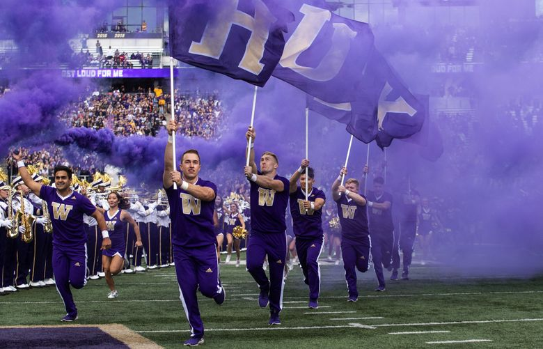 Washington's cheerleaders lead the team out onto the field against USC on Saturday, September 28, 2019 at Husky Stadium.  (Dean Rutz / The Seattle Times)