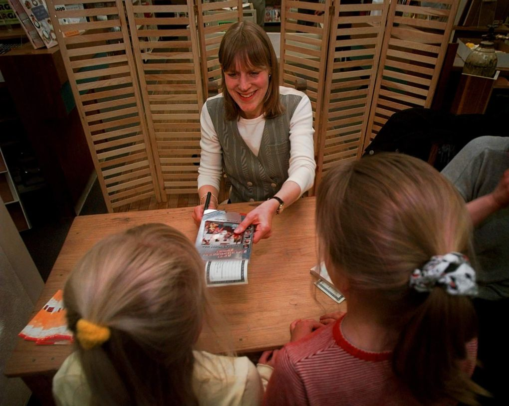 """In this file photo, bestselling author Ann M. Martin signs one of her new books for Rebecca Gregg, then 7, and Taylor Schlosser, 8, during her appearance at an Albuquerque, New Mexico bookstore in April 1997. Drawing on her own experiences, Martin's """"The Baby-Sitters Club"""" book series was a hit with children in the 1990s, and was recently rebooted by Netflix. (AP Photo / Eric Draper)"""