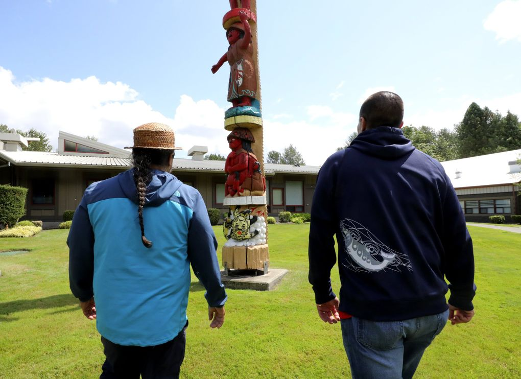 Hanford McCloud, left, and Willie Frank III approach the totem pole in front of the Wa-He-Lut Indian School at Frank's Landing. (Alan Berner / The Seattle Times)