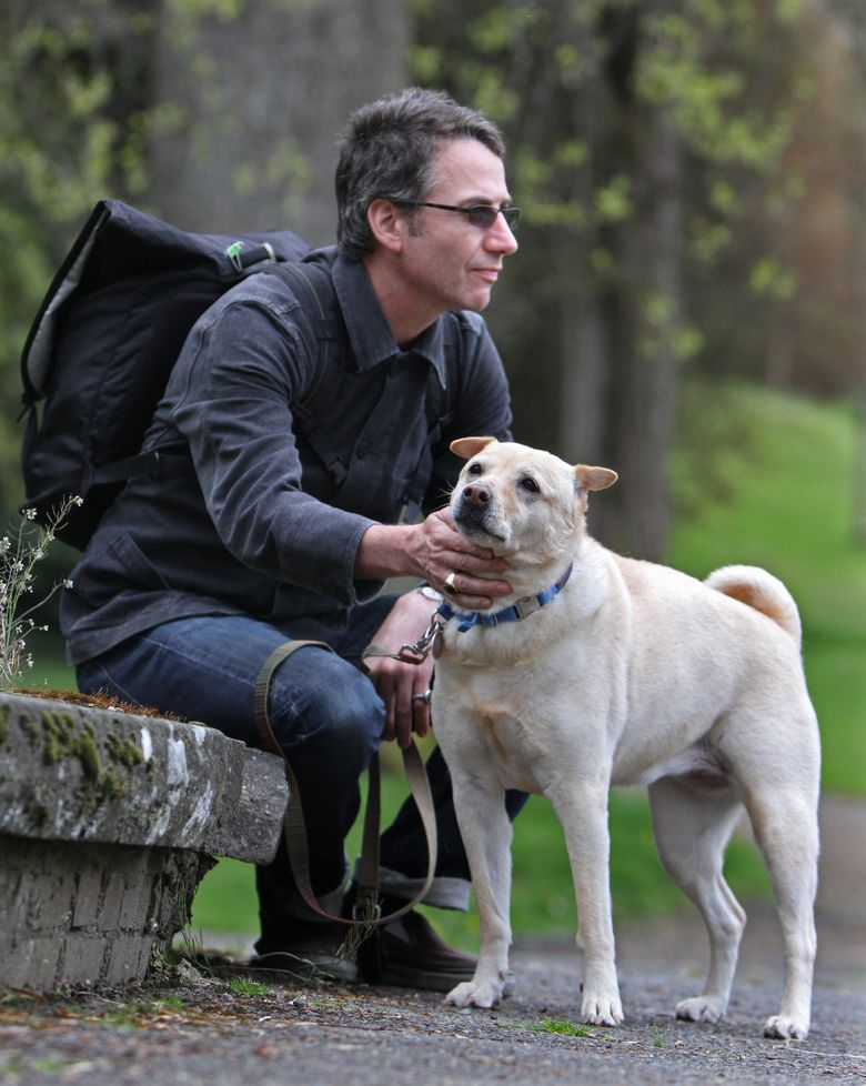 """In this 2011 file photo, Pearl Jam guitarist Stone Gossard takes his dog Basie for a walk. The born-and-raised Seattleite recommends folks read the Rachel Cusk """"Outline"""" trilogy. (Steve Ringman / The Seattle Times, file)"""