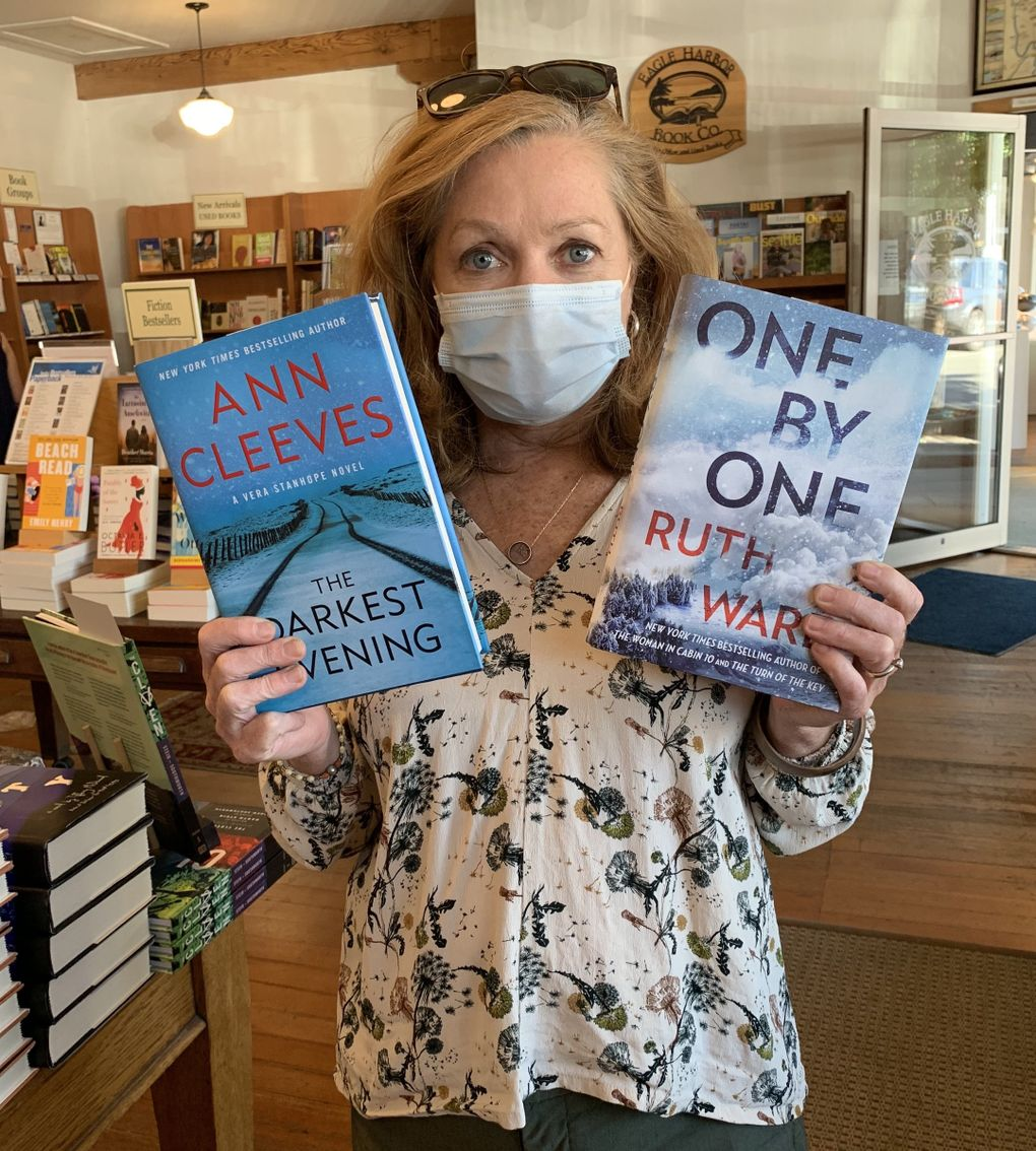Eagle Harbor Book Company owner Jane Danielson shows off a couple of bestselling titles at her Bainbridge Island bookstore, which also counts among its bestsellers titles from the dense literary talent pool on the island itself. (Courtesy of Eagle Harbor Books)