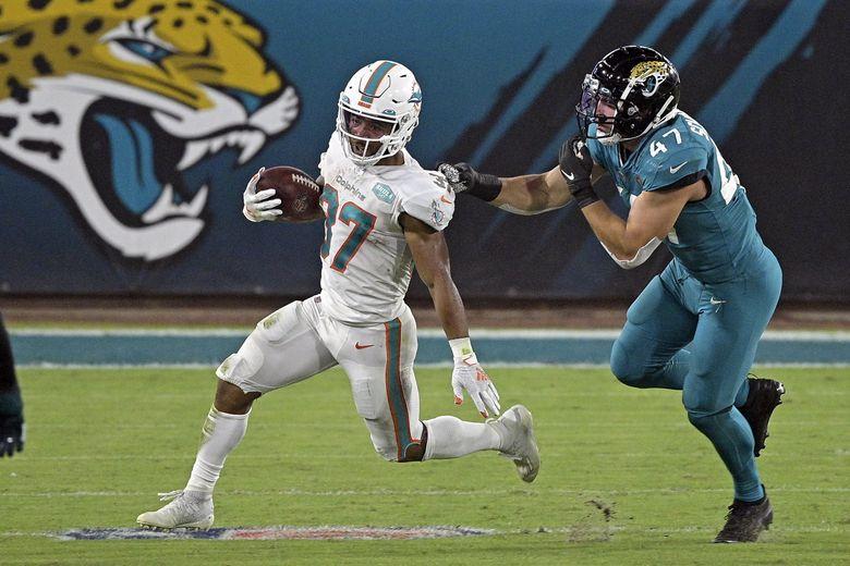 Former UW and current Miami Dolphins running back Myles Gaskin, left, runs past Jacksonville Jaguars middle linebacker Joe Schobert in the first half last Thursday in Jacksonville, Florida. (Phelan M. Ebenhack / The Associated Press)