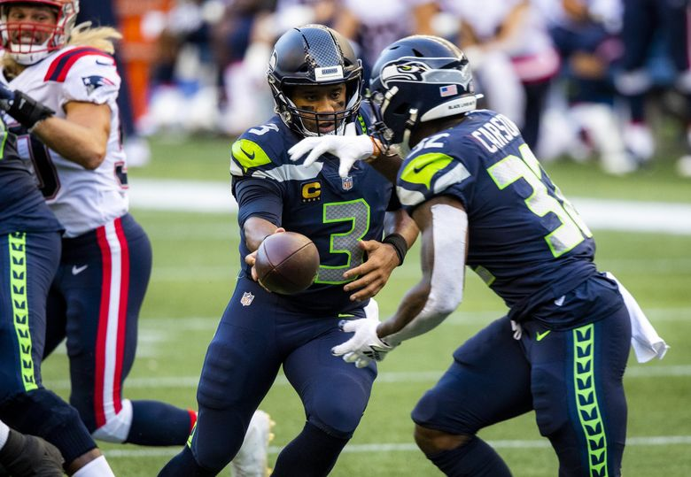 Seahawks quarterback Russell Wilson hands off to running back Chris Carson last Sunday against the Patriots at CenturyLink Field. (Bettina Hansen / The Seattle Times)