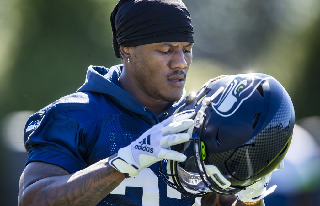 Seahawks running back Chris Carson puts his helmet on at training camp Aug. 28. (Bettina Hansen / The Seattle Times)