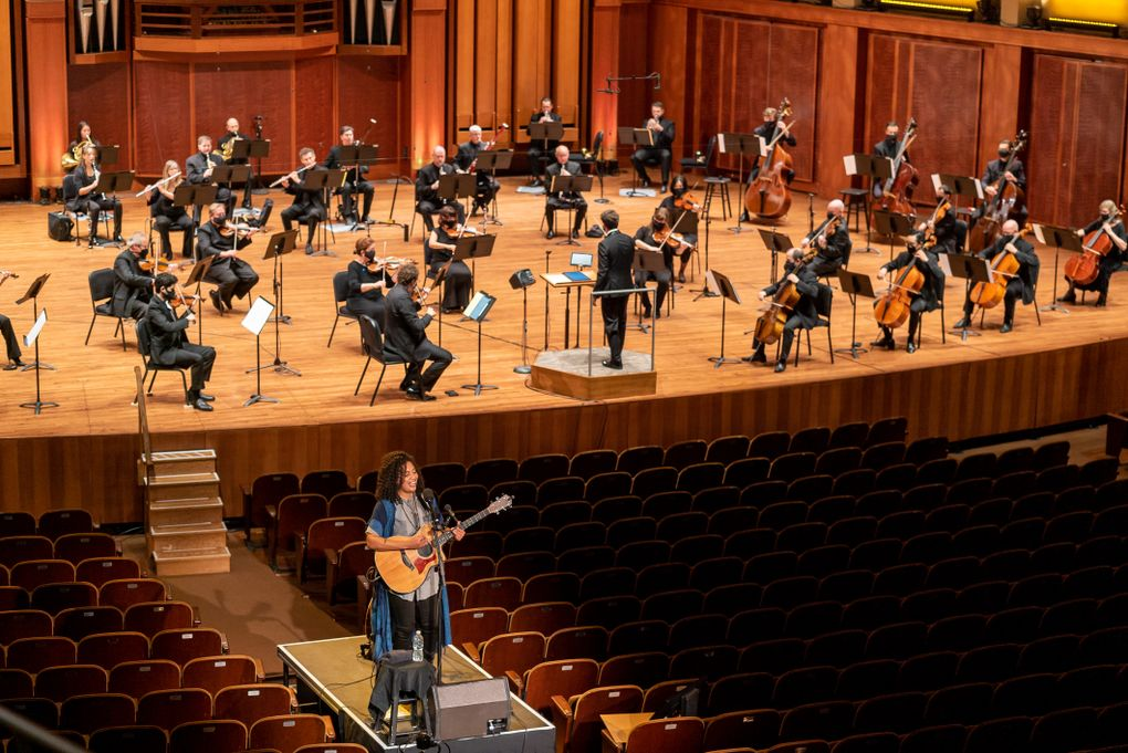 Seattle singer-songwriter Whitney Mongé performs at a distance from the Seattle Symphony musicians during the opening-night performance. (James Holt / Seattle Symphony)