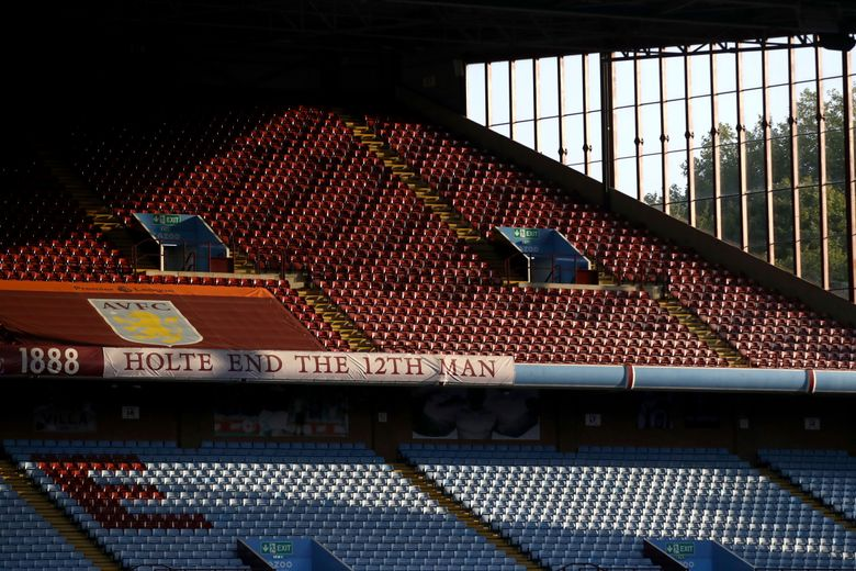FILE – In this Monday, Sept. 21, 2020 file photo, the sun illuminates the empty stands before the English Premier League soccer match between Aston Villa and Sheffield United at the Villa Park stadium in Birmingham, England. Every empty seat in a Premier League stadium represents a visual reminder of the financial struggle many soccer teams are facing amid the coronavirus pandemic. For smaller soccer teams without TV contracts and huge fan bases, empty seats at matches amid the pandemic can have devastating financial implications. (Tim Goode/Pool via AP, File)