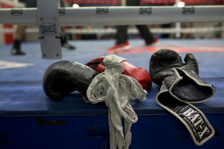 FILE – In this Friday, April 29, 2016 file photo, boxing gloves lie on a boxing ring as boxers work out at El Rayo boxing gym in Madrid, Spain. Journeymen fighters like Jamie Quinn regularly rack up losses in British boxing. They're hired to fight up-and-comers who are unbeaten or looking to bolster their resumes. Wins are few and far between. The 30-year-old Quinn has a record of seven wins, 104 losses and two draws. He has fought and lost twice since boxing events returned from the pandemic stoppage. (AP Photo/Francisco Seco, File)