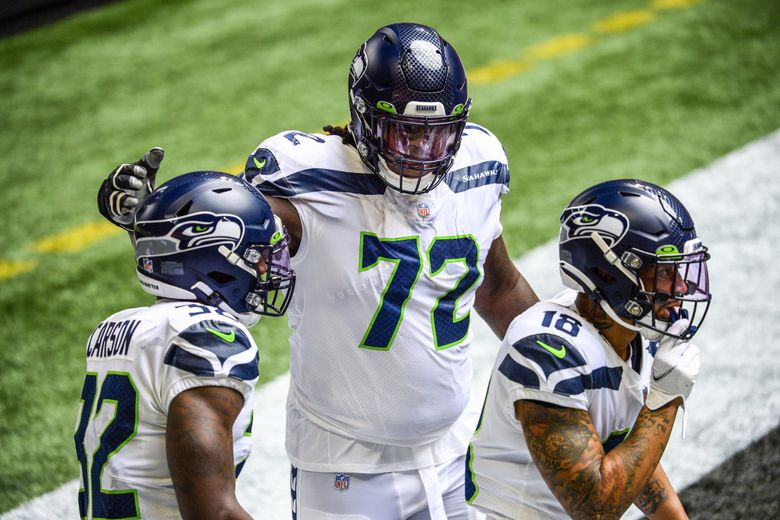 """Seahawks offensive tackle Brandon Shell (72) celebrates a touchdown by running back Chris Carson (32) and wide receiver Freddie Swain (18) against the Atlanta Falcons on Sept. 13 in Atlanta. Shell has partnered with The Stuttering Association for the Young to encourage kids with a speech impediment: """"It's not going to stop you or it's not going to define you from what you want to be in life."""" (Danny Karnik / AP)"""