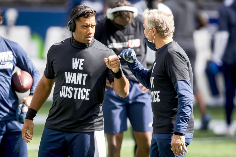 Russell Wilson and head coach Pete Carroll fist bump during warmups before the Seahawks played the Dallas Cowboys on Sept. 27 in Seattle. (Bettina Hansen / The Seattle Times)