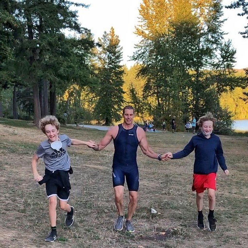 """Jimmy Watts finishes his """"Solo Man"""" triathlon at Lake Padden in Bellingham on Sept. 6 while holding hands with his sons, Taylor (left) and Cody (right).  (Photo courtesy Jimmy Watts / )"""