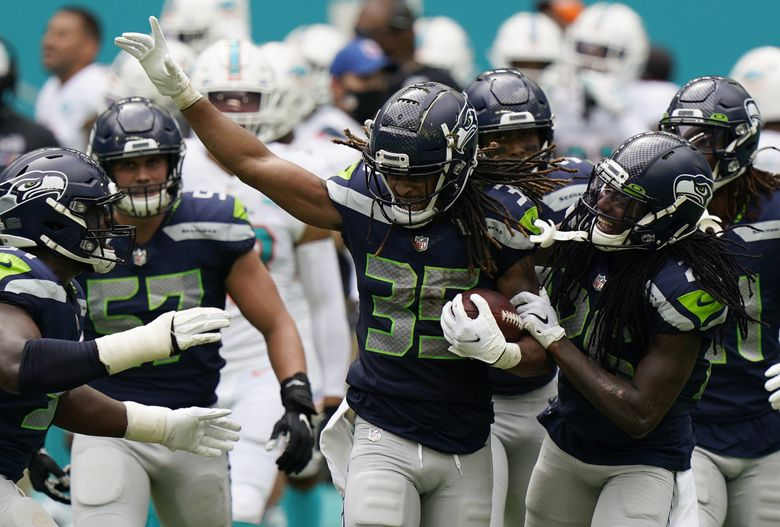 Seahawks cornerback Ryan Neal (35) celebrates with teammates after intercepting a pass in the first half Sunday against the Dolphins in Miami Gardens, Florida. Neal started the game at safety in place of the injured Jamal Adams. (Wilfredo Lee / AP)