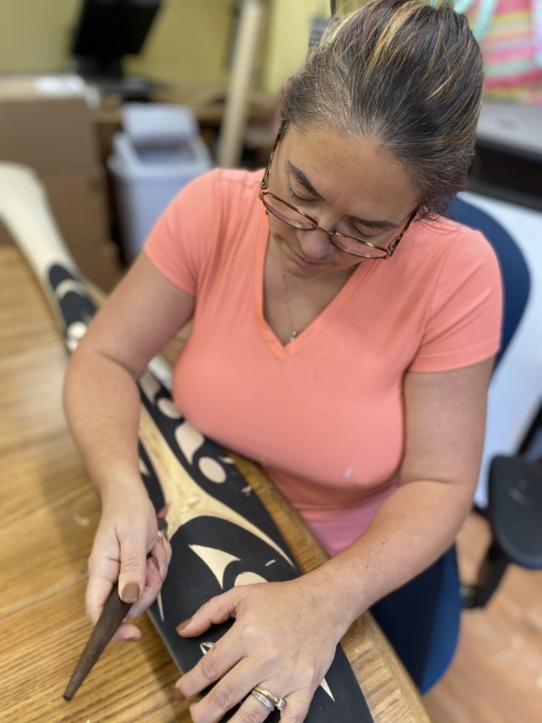 Carver Andrea Wilbur-Sigo at work. The artist is in the process of designing a welcome figure to accompany a new mixed-use building in downtown Seattle that will include affordable housing for Native Americans. (Florence Sigo)