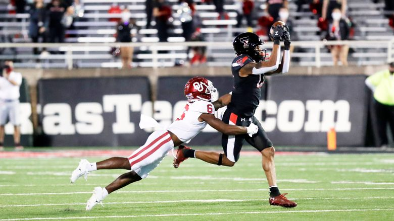 Texas Tech wide receiver Erik Ezukanma makes a reception while covered by Oklahoma cornerback Tre Brown in the first half of a game last October in Lubbock, Texas. (Mark Rogers / AP)