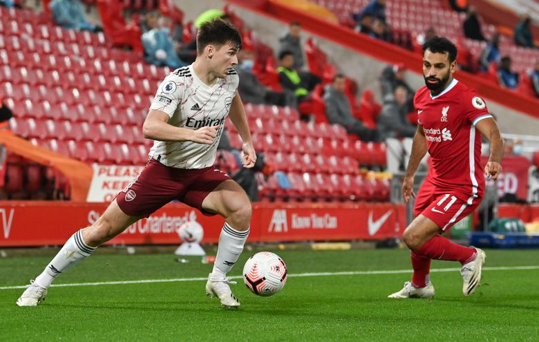 Arsenal's Kieran Tierney, left, looks t take the ball past Liverpool's Mohamed Salah during the English Premier League soccer match between Liverpool and Arsenal at Anfield in Liverpool, England, Monday, Sept. 28, 2020. (Paul Ellis/Pool via AP)
