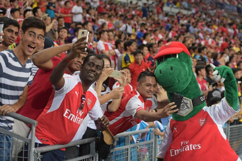 FILE – In this Saturday, July 18, 2015 file photo, fans pose for pictures with Arsenal's mascot Gunnersaurus ahead of their team's soccer match against Everton for the Barclays Asia Trophy in Singapore. Out-of-favor Arsenal playmaker Mesut Ozil wants to save Gunnersaurus from extinction. Ozil expressed sadness Tuesday Oct. 6, 2020, after discovering that Jerry Quy — the man who fills the Arsenal dinosaur mascot outcut — had been made redundant by the London club after 27 years. (AP Photo/Joseph Nair, File)