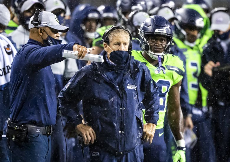 Defensive coordinator Ken Norton Jr. talks with Seahawks head coach Pete Carroll with the rain pouring down and the Vikings poised to score in the fourth quarter as the Seattle Seahawks take on the Minnesota Vikings at CenturyLink Field in Seattle Sunday October 11, 2020. (Bettina Hansen / The Seattle Times)