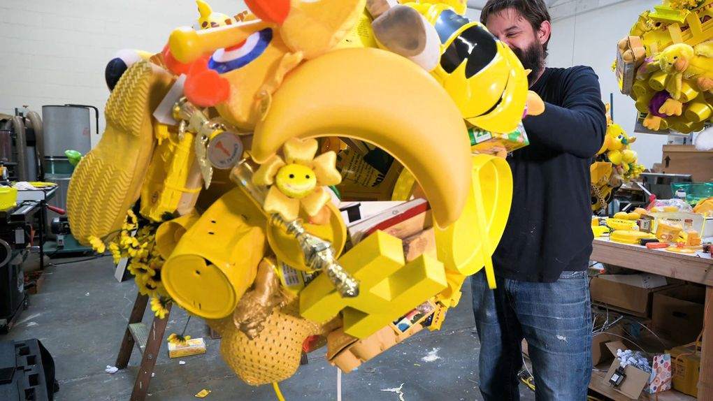 """Ben Beres of the Seattle-based art collective SuttonBeresCuller works on part of the trio's installation for Bellevue Arts Museum's """"Yellow No. 5,"""" curated by Tariqa Waters. (Emilie Smith)"""