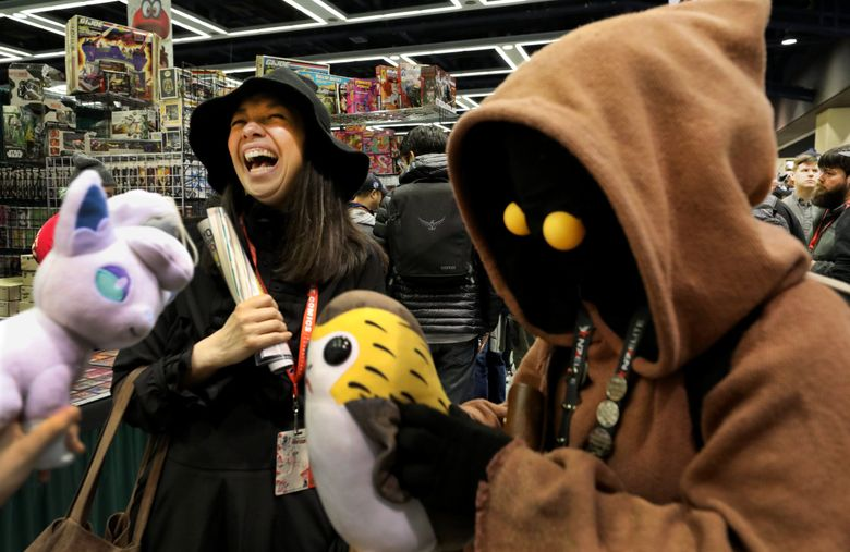 """Michaele Razi, left, dressed as a witch from Harry Potter, gets a kick out of Jackie Yeo's """"Star Wars"""" Jawa outfit at the 2019 Emerald City Comic Con. (Alan Berner / The Seattle Times)"""