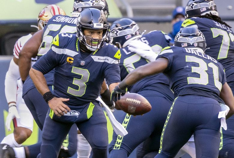 Russell Wilson hands off to DeeJay Dallas, who had 41 yards rushing and two touchdowns in Sunday's win over the San Francisco 49ers. (Dean Rutz / The Seattle Times)