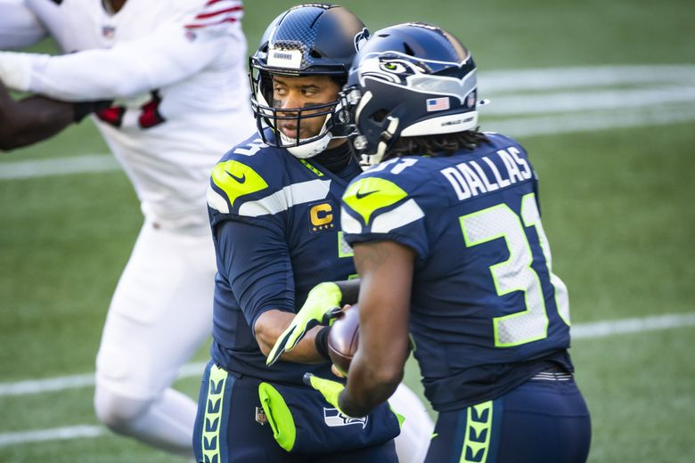Seahawks quarterback Russell Wilson hands off to rookie running back DeeJay Dallas as the Seattle Seahawks take on the San Francisco 49ers at CenturyLink Field in Seattle November 1, 2020.  (Bettina Hansen / The Seattle Times)