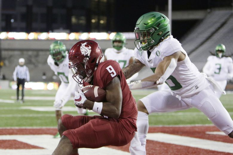 Washington State wide receiver Renard Bell, left, catches a pass for a touchdown in front of Oregon safety Nick Pickett during the first half of an NCAA college football game in Pullman, Wash., Saturday, Nov. 14, 2020. (Young Kwak / The Associated Press)