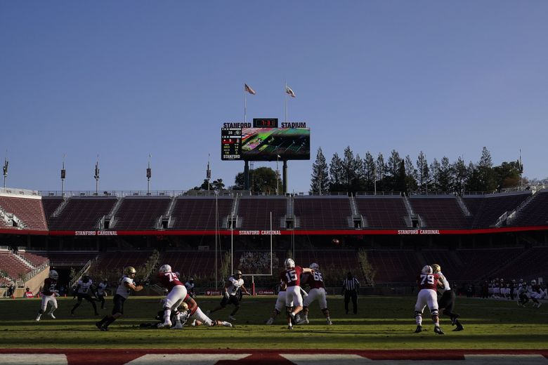 Stanford quarterback Davis Mills (15) passes against Colorado in front of empty seats at Stanford Stadium during the second half of an NCAA college football game in Stanford, Calif., Saturday, Nov. 14, 2020.  (Jeff Chiu / AP)